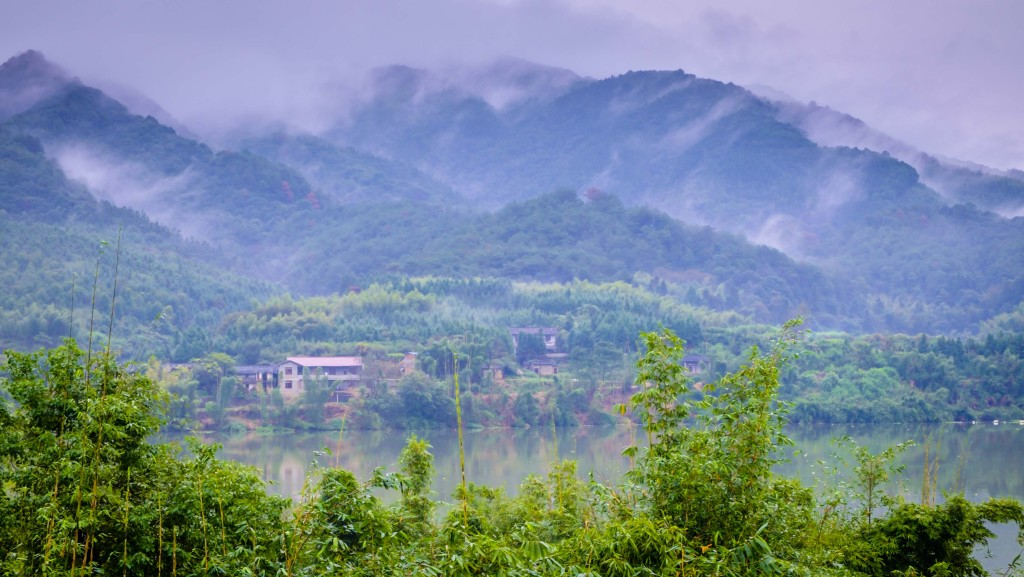 Mists cling to the mountains above the tiny village.